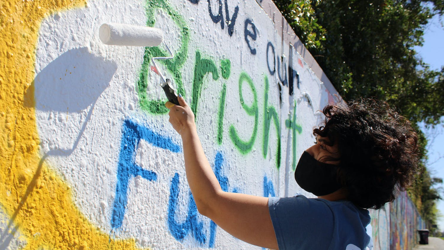 "Alondra Arce, 20, a UF sustainability sophomore, paints a mural that says ""Save Our Bright Futures"" on Sunday, March 7, 2021. Arce recruited student volunteers to help her create the mural along 34th Street in Gainesville to raise awareness about Senate Bill 86, which would limit some students' access to state funding for college if passed."