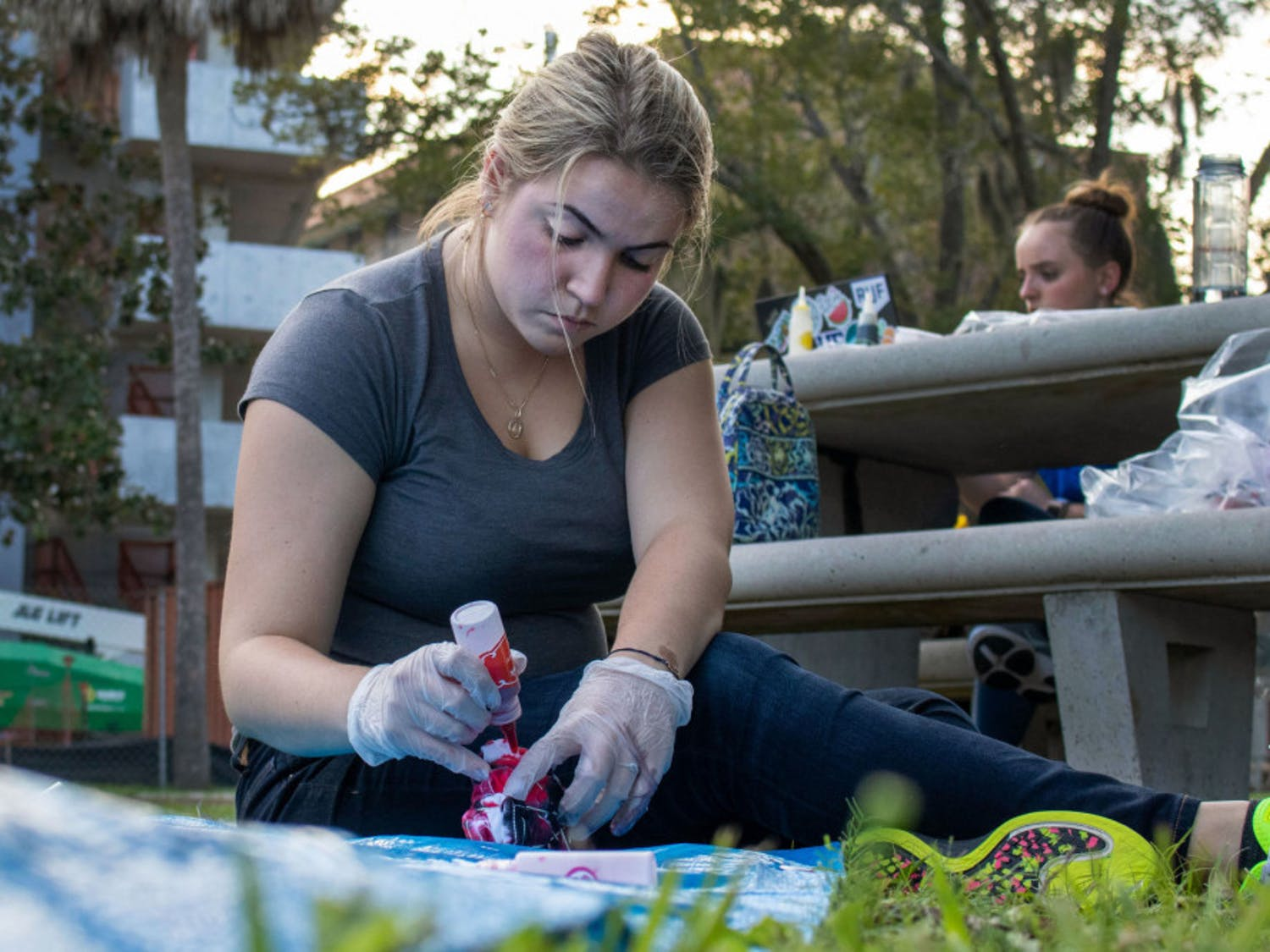 Andrea Lopez, an 18-year-old biomedical engineering freshman at the University of Florida, tie-dyes a shirt Thursday evening during an event for the SWEek of Welcome on the Reitz North Lawn. Lopez said she heard about SWE during E-Swamp and decided she wanted to be a member.