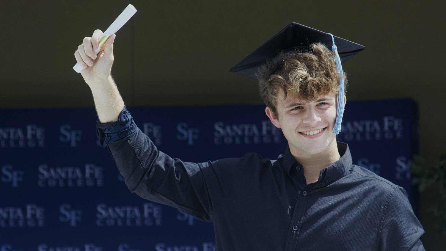 Alexander McCollum, 19, a Santa Fe Associate of Arts graduate stands through the sunroof of a white limousine with his hand holding a paper scroll raised in the air in celebration during Santa Fe College's Drive-Thru Grad Walk ceremony on Thursday, April 29, 2021.