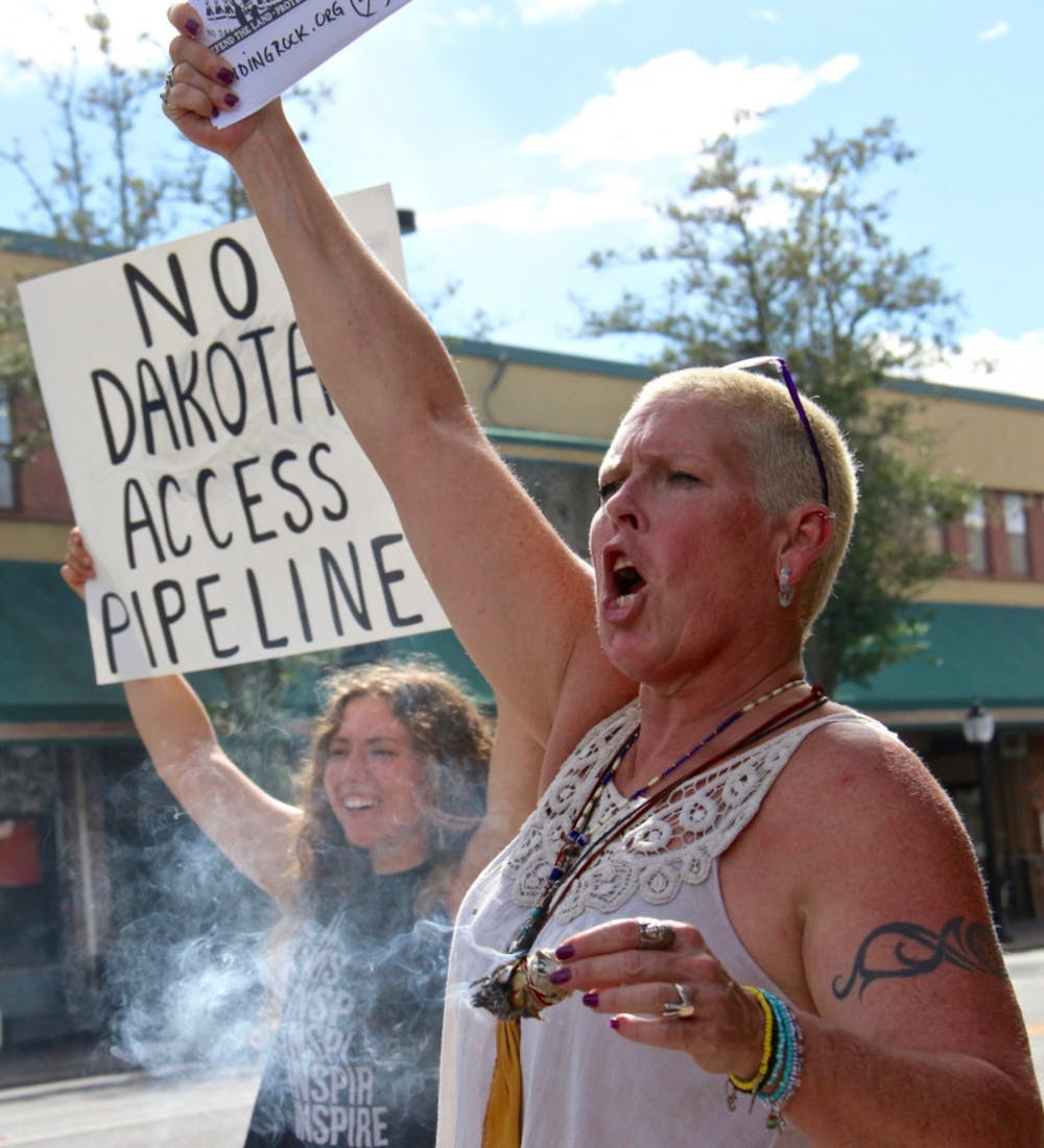 """<p dir=""""ltr""""><span>Burning sage, which is sacred to Native Americans, on the corner of University Avenue and Main Street, Marci Munden chants for clean water for the Dakota people. """"This is sacred work,"""" Munden, 53, said of protesting the proposed oil pipeline in North Dakota.</span></p><p><span></span></p>"""