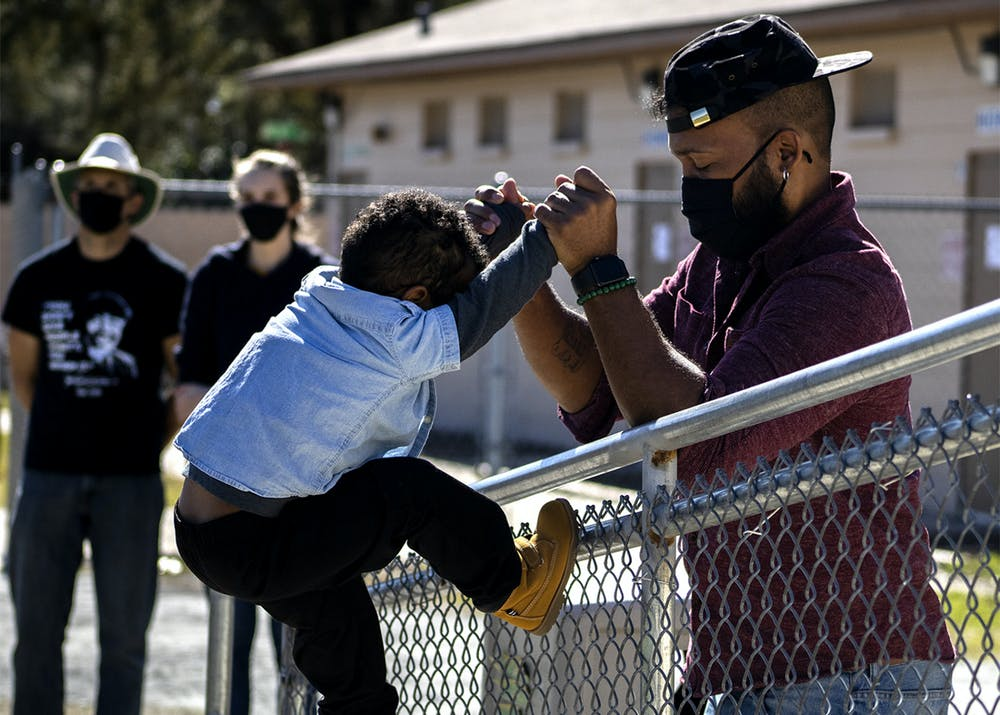 """Ryan Hope Travis helps his 2-year-old son, Rezen Hope Travis, climb a fence at the King Celebration at Citizens Field on Monday, Jan. 18, 2021. Ryan Hope Travis said it was the first Martin Luther King Jr. Day celebration Rezen was old enough to understand. """"Him knowing his history is the foundation of him being able to grow,"""" he said."""