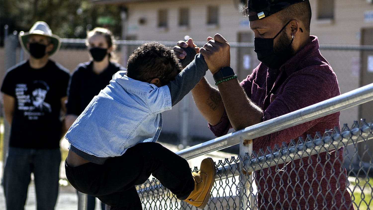 "Ryan Hope Travis helps his 2-year-old son, Rezen Hope Travis, climb a fence at the King Celebration at Citizens Field on Monday, Jan. 18, 2021. Ryan Hope Travis said it was the first Martin Luther King Jr. Day celebration Rezen was old enough to understand. ""Him knowing his history is the foundation of him being able to grow,"" he said."