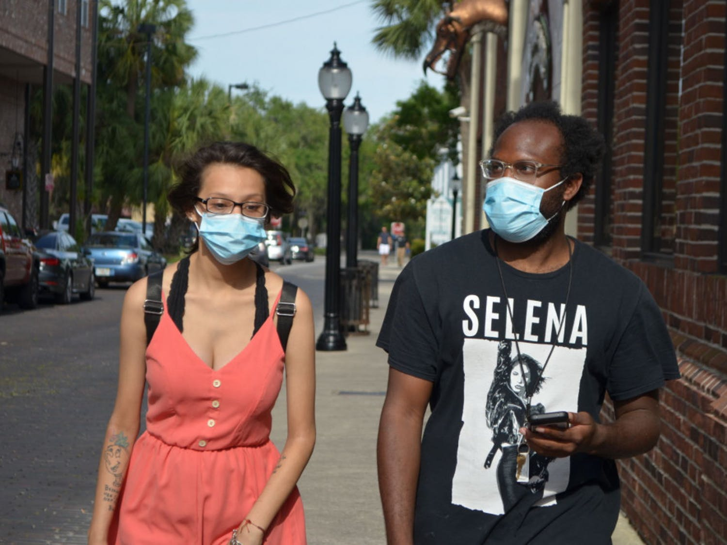 Denise Garcia and Jeffery Davis wear face masks in downtown Gainesville. The commission voted Tuesday to end the face mask requirement in its emergency order.