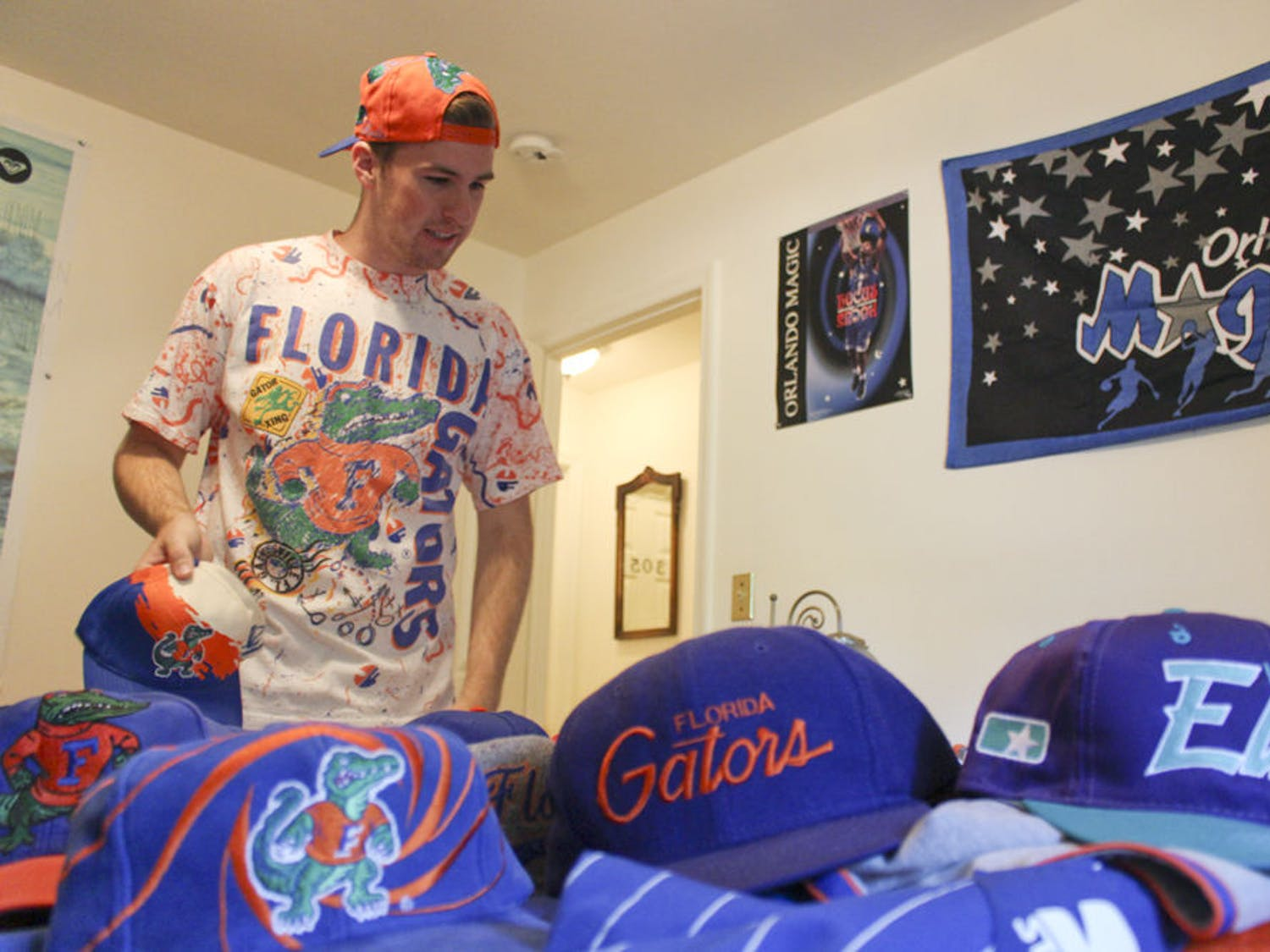 "Josh Rittenour, a 20-year-old UF economics junior, lays out a portion of sports hats that he has collected through thrifting at his house on Sept. 24, 2015. Rittenour restores the old hats. ""It's something that I have and can bring back to life and let someone else enjoy as much as the original person,"" he said."