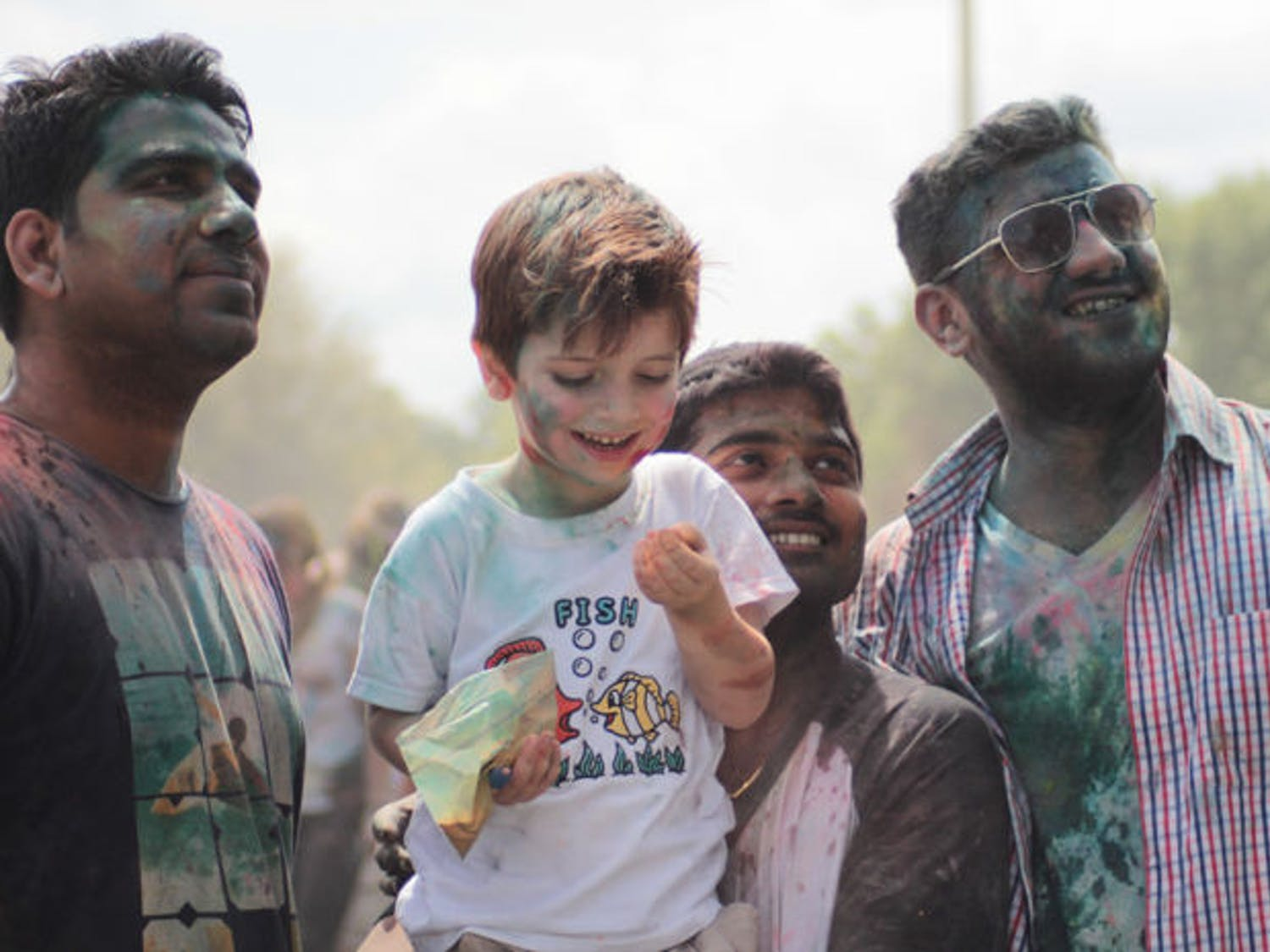 Covered with colored powder and mud, UF Holi Festival of Colors participants watch the festival unfold Saturday on Flavet Field. Holi is one of the major religious festivals in India.