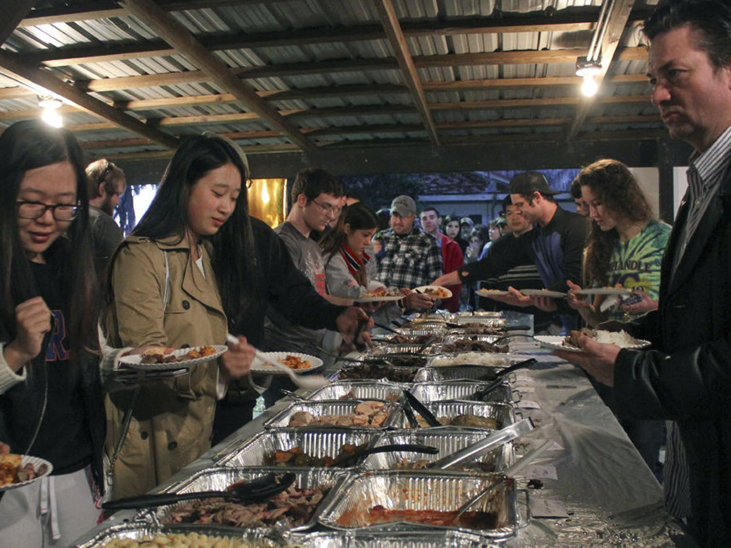 Fan Zhang (left), 24, and Xuesong Ding, 21, both UF urban and regional planning students, and Darren Lane, 44, fill plates from a buffet including buffalo, python and elk meat Saturday during the Beast Feast, a fundraising dinner held by the UF Wildlife society at Whitehurst Lodge in Archer. For video coverage of the event, visit www.alligator.org.