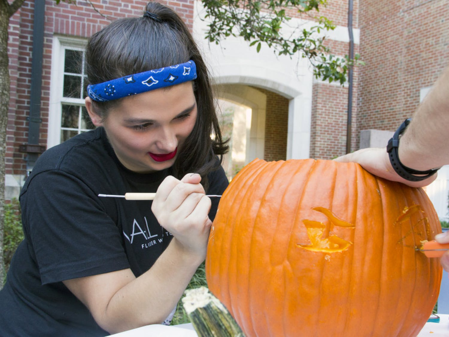 Rhyan Nedobity, a 19-year-old UF accounting sophomore, carves a pumpkin monday during the Pumpkin Palooza Leadership Venture at the Heavener Hall courtyard. Hosted by the Warrington Diplomats, the organization holds events that focus on professional development every semester.