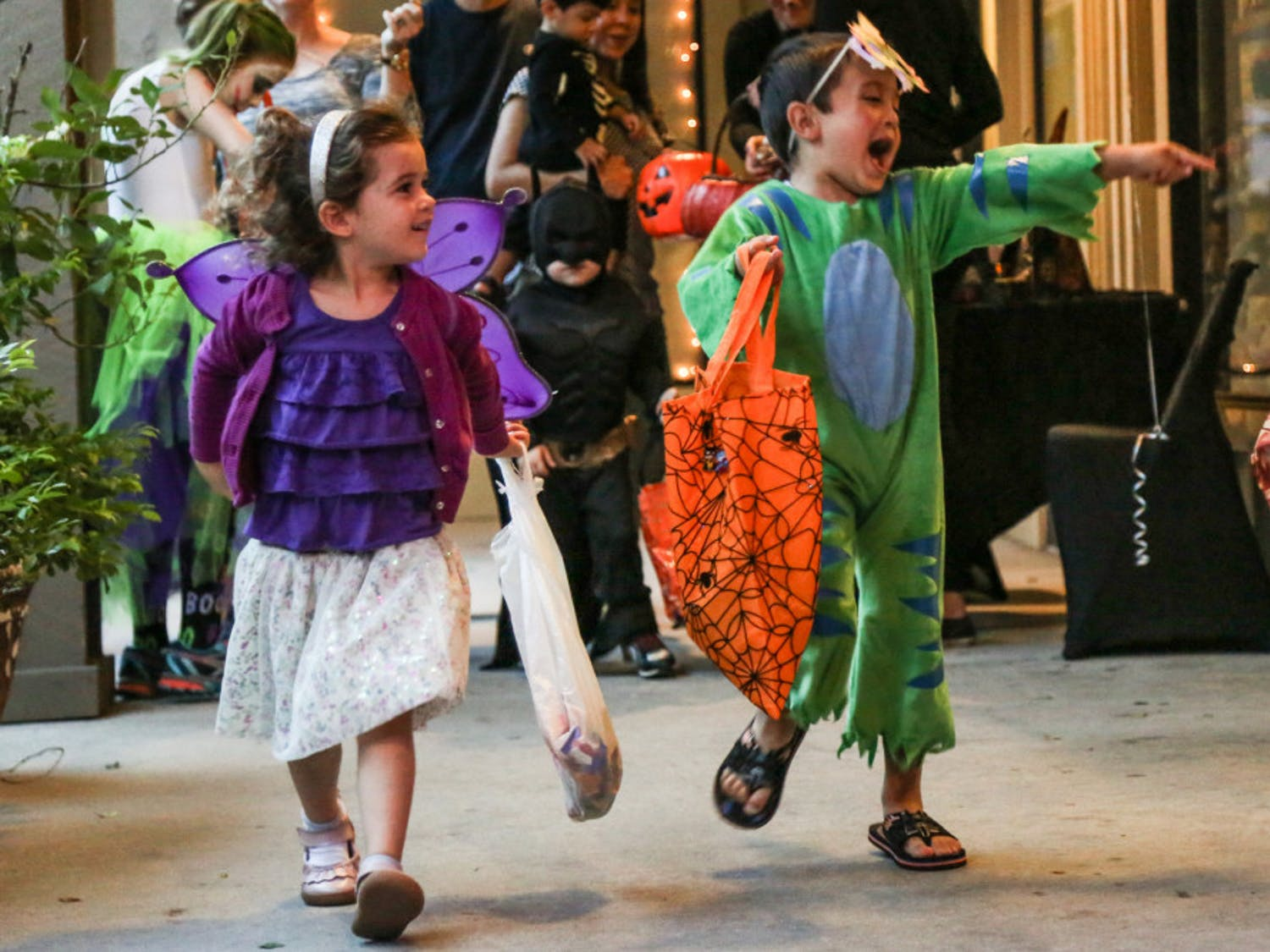 From left: 4-year-old Lilla Hall, dressed like a fairy, and 4-year-old Omar Saab, who wore a dinosaur costume, walked while they trick-or-treated at Flying Biscuit Cafe on 2441 NW 43rd St. on Thursday evening.