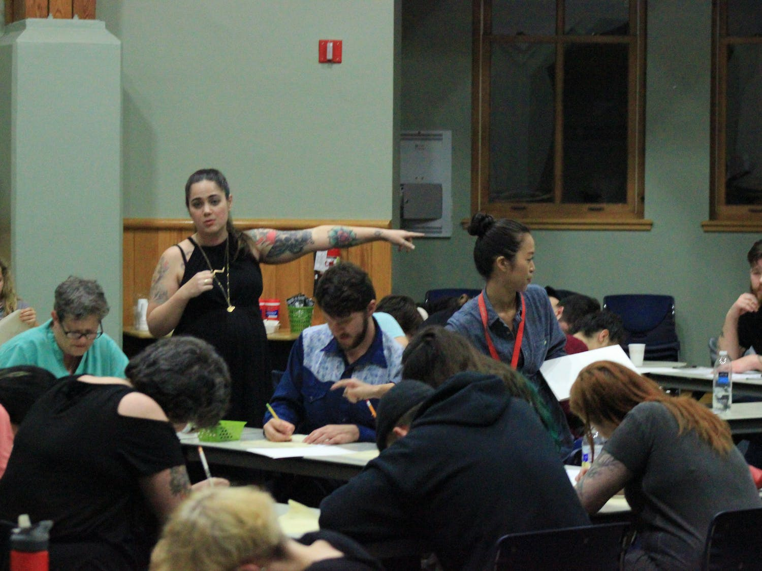 """Standing to the left, Kristyn """"Bat"""" Lopez, a tattooist for Death or Glory Tattoo, directs her Thursday night flash-tattoo workshop class at Alachua County Public Library's Headquarters Branch to drawing supplies."""