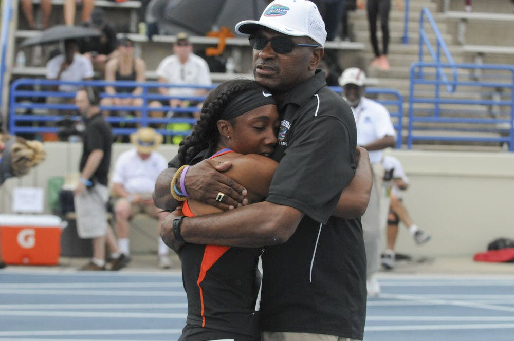 <p>Robin Reynolds hugs coach Mike Holloway after winning the 400-meter dash at Friday's Pepsi Florida Relays on the Percy Beard Track.</p>