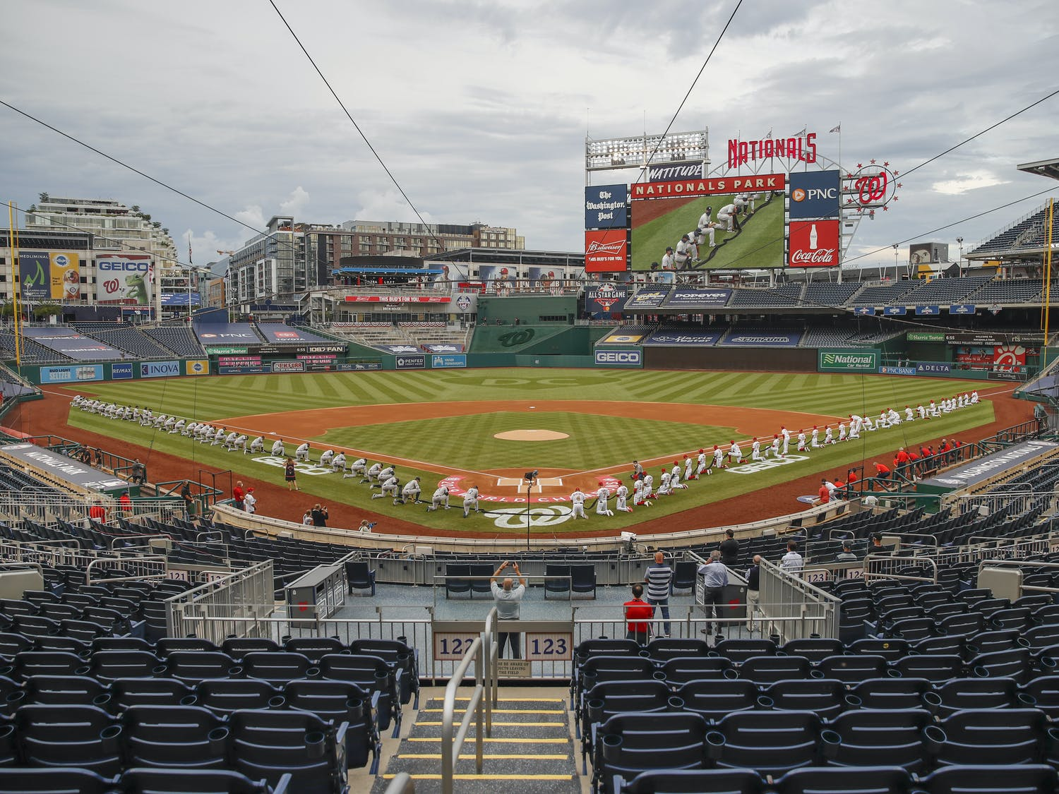 The New York Yankees and the Washington Nationals kneel while holding a black ribbon to honor Black Lives Matter before playing an opening day baseball game at Nationals Park, Thursday, July 23, 2020, in Washington. before the start of the first inning of an opening day baseball game at Nationals Park, Thursday, July 23, 2020, in Washington. (AP Photo/Alex Brandon)