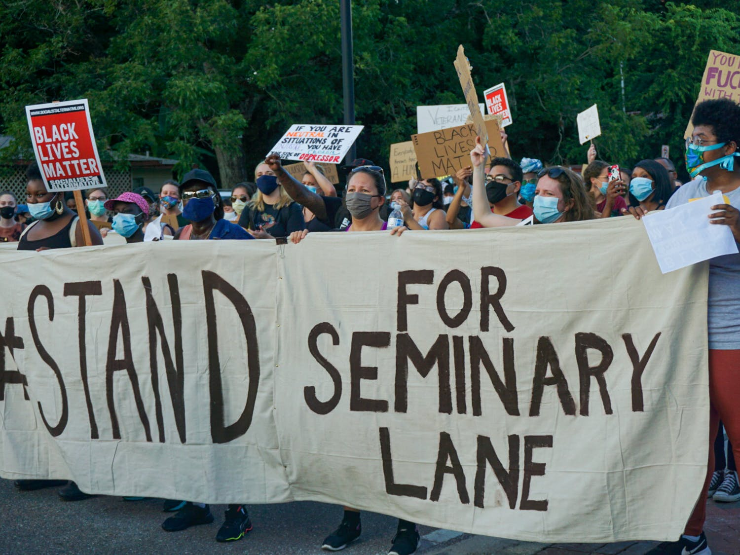 """Protesters hold a banner that reads, """"#StandForSeminaryLane,"""" demanding that developers refrain from building luxury student apartments on land located in a historically Black community."""