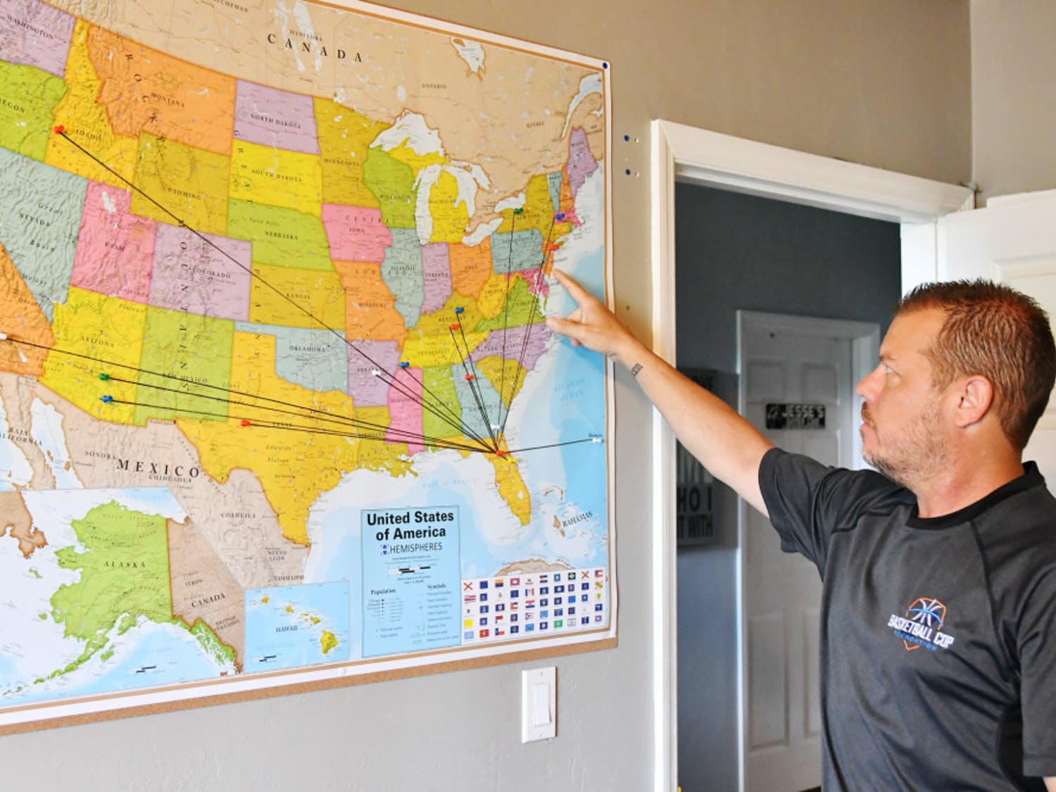 Pointing at a map dotted with colored pushpins, Gainesville Police Officer Bobby White shows where he has delivered basketball hoops and balls as part of his Basketball Cop Foundation.