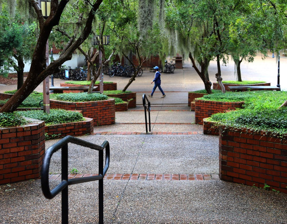 <p>A lone man is seen walking through Turlington Plaza at UF in Gainesville, Fla., on August 31, 2020. The plaza, which is usually filled with people, remained relatively bare on the first day of fall classes.</p>