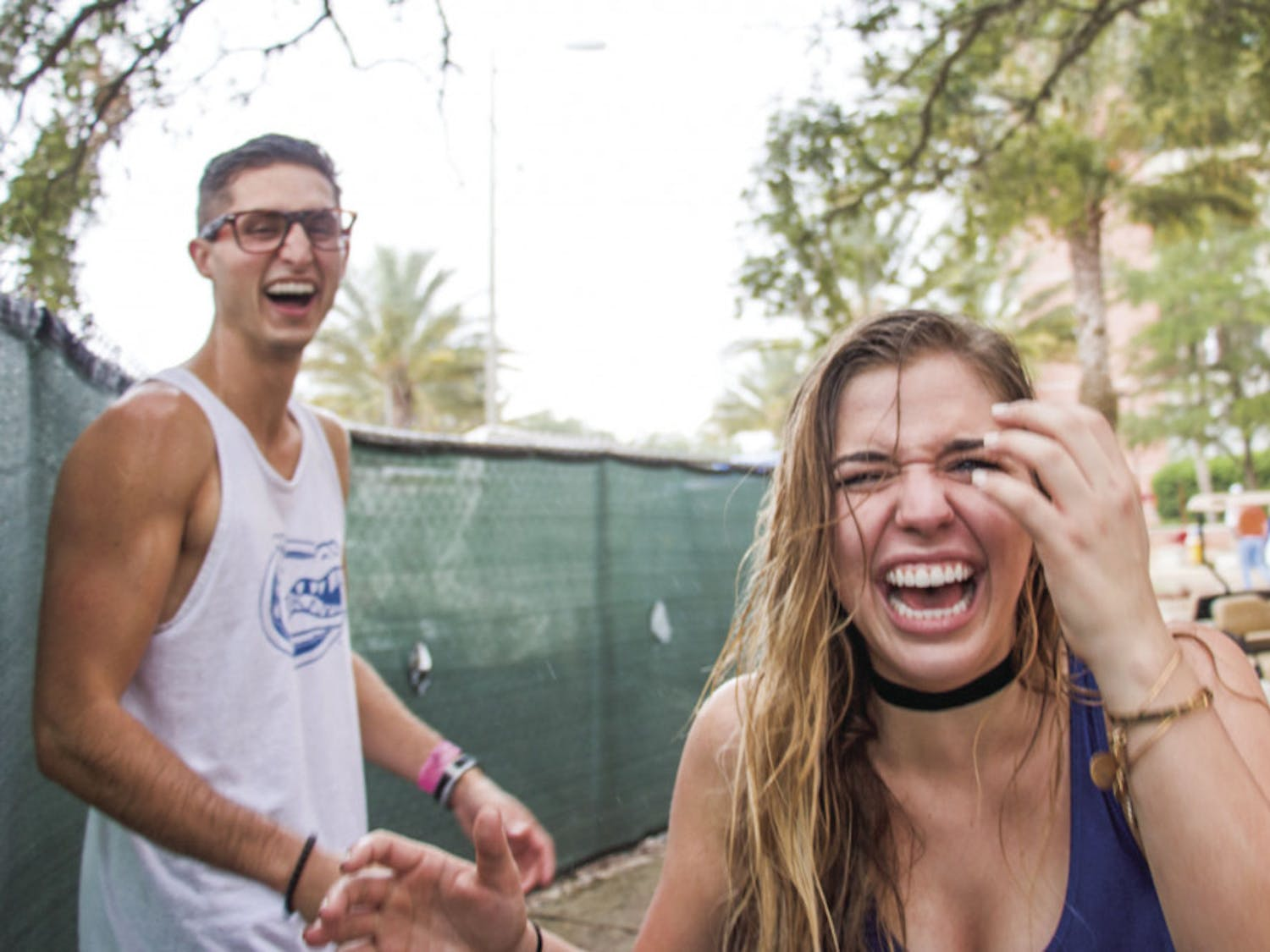 "From left: UF students Richard Minichiello and Sarah Galante laugh while facing the rain before the UF Homecoming football game on Saturday afternoon. They ""couldn't believe they got soaked,"" said Galante."