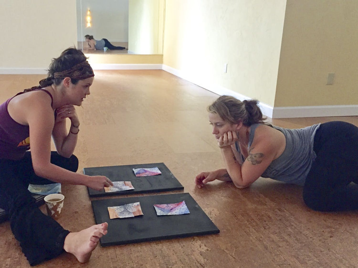 Jenna Horner, left, shows samples of the art she is making for her yoga instructor, Samantha Jones. Horner is a Gainesville-based multimedia artist who incorporates people's belongings into her works.