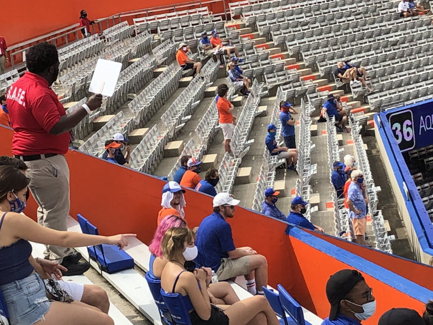 A S.A.F.E. staff member instructs fans in the student section to put on their masks at Saturday's home opener in Ben Hill Griffin Stadium.