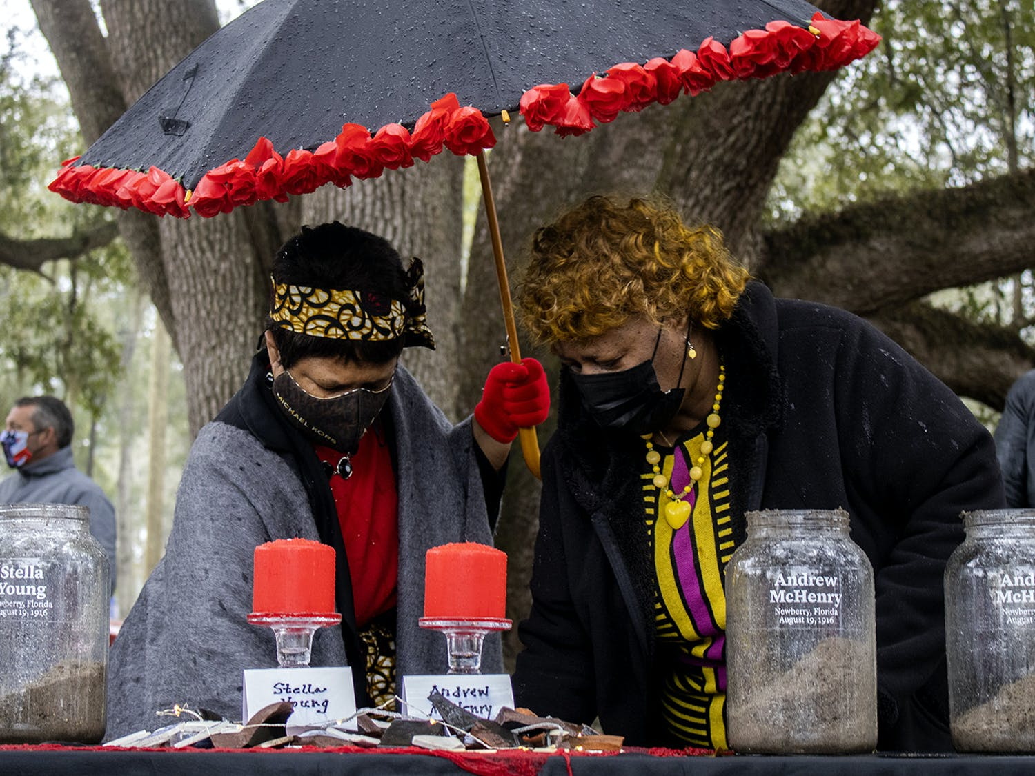 Gail K. Watson (left) and Brenda Whitfield (right) scoop dirt into glass jars at the soil ceremony for the Newberry Six on Friday, Feb. 5, 2021. Whitfield spoke during the ceremony before the crowd began adding earth to the containers.
