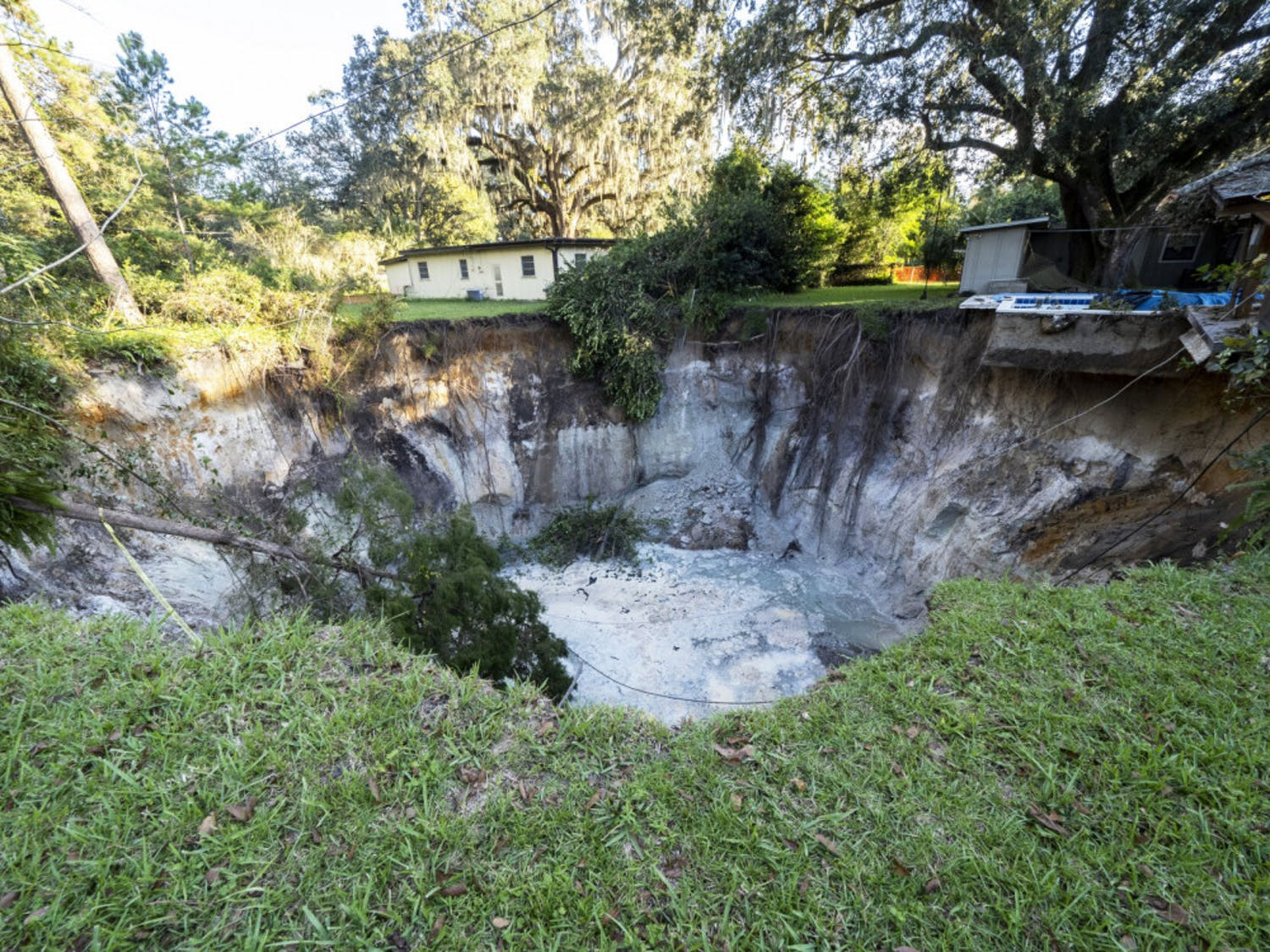 A sink hole that appeared during the week is seen behind NW 14th Place on Sunday, Oct. 25, 2020. People who live in the homes surrounding the sinkhole were asked to evacuate this past Thursday.