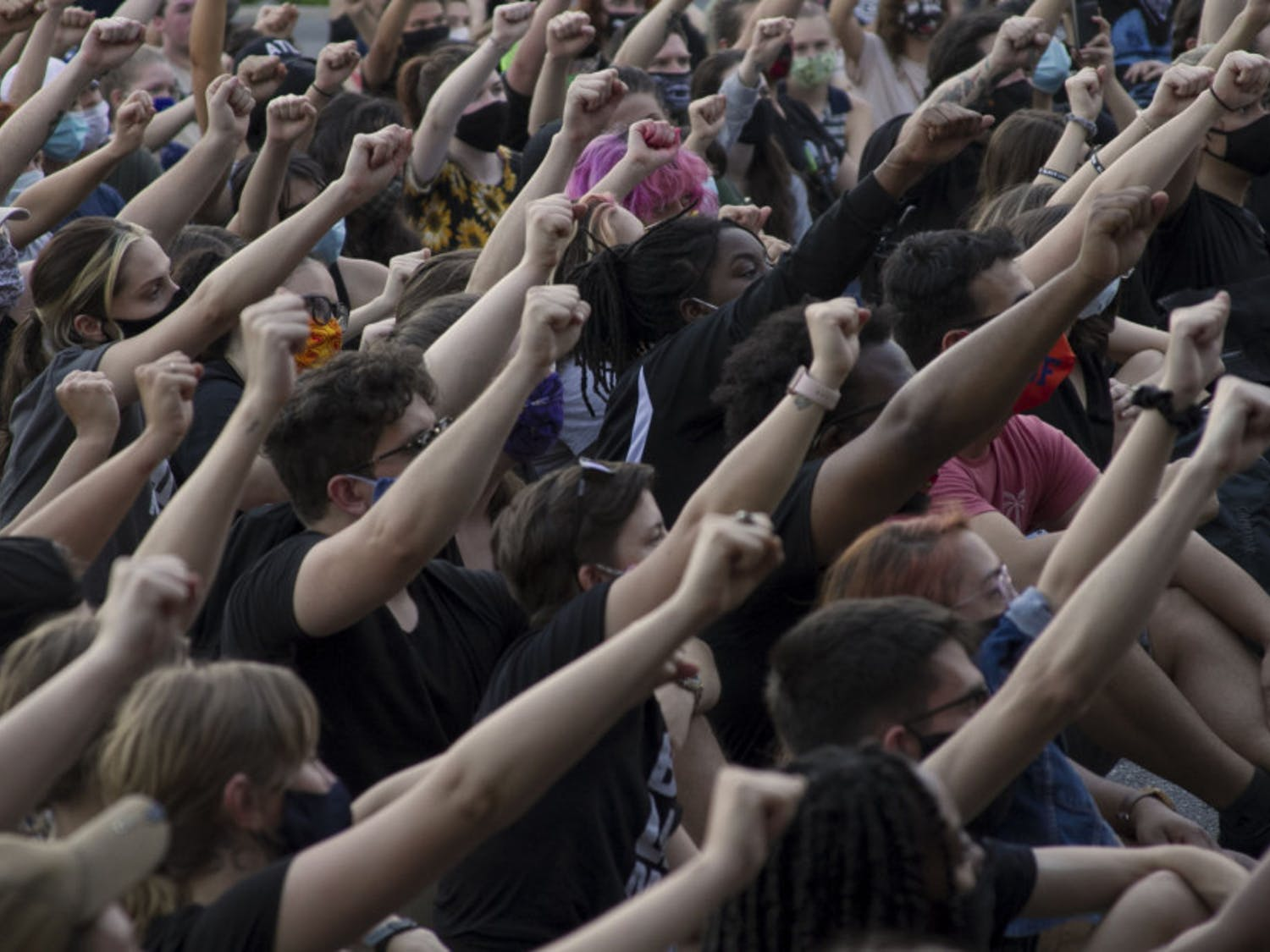 """GoDDsville Dream Defenders use the stop at the Gainesville Police Department to announce a list of demands that the organization will present to local government officials. Hundreds of fists rise into the air as the crowd chants """"No justice, no peace."""""""