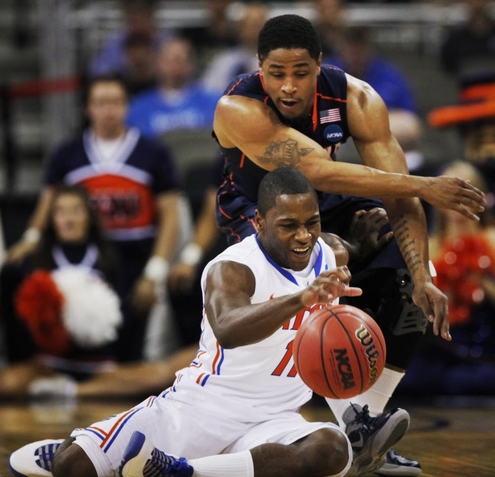 <p>Florida guard Erving Walker (11) controls the ball while covered by Virginia guard Jontel Evans (1) during the first half of a second-round NCAA college basketball tournament game at CenturyLink Center in Omaha, Neb., Friday, March 16, 2012. (AP Photo/Nati Harnik)</p>