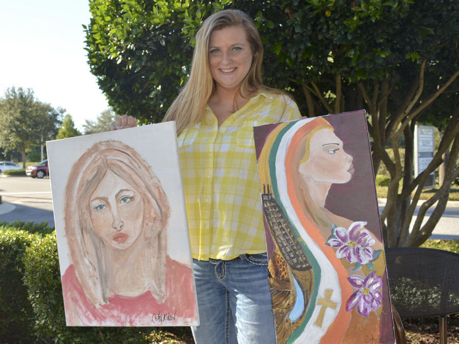"""Charissa Krasnow, 35, holds up her two self portraits outside of Starbucks at Tioga Town Center. The left portrait is untitled, and """"Warrior"""" is a mixed-media piece."""