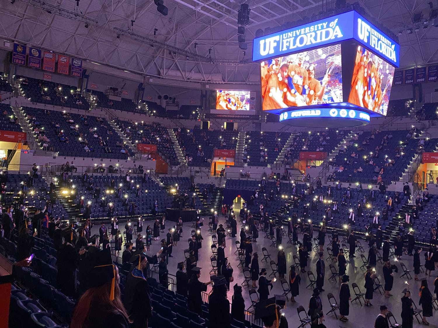 """UF graduates stand and sing along to Tom Petty's """"I Won't Back Down"""" during the 2021 graduation ceremony on Saturday, May 1, 2021. (Photo by Makiya Seminera)"""