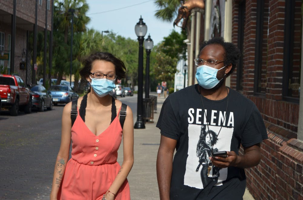 <p>Denise Garcia and Jeffery Davis wear face masks in downtown Gainesville.</p>
