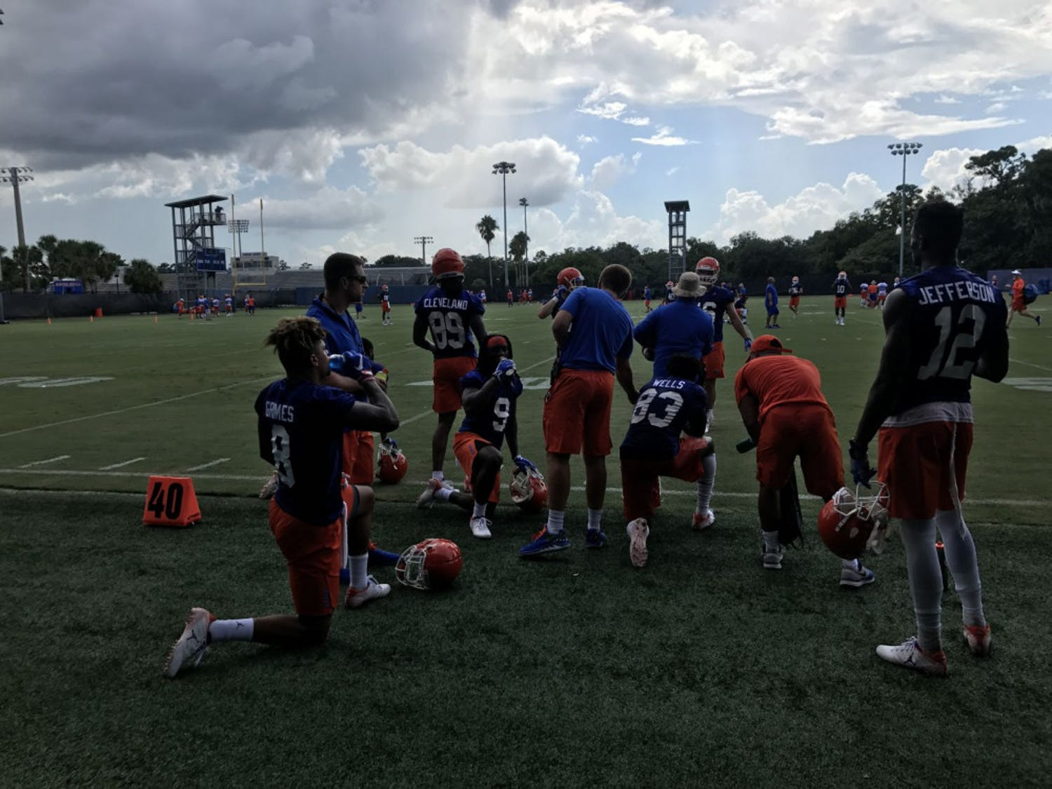 A unit of Florida wide receivers, including transfers Van Jefferson (12) and Trevon Grimes (8), rests during Day 1 of fall camp after catching passes from the quarterbacks.