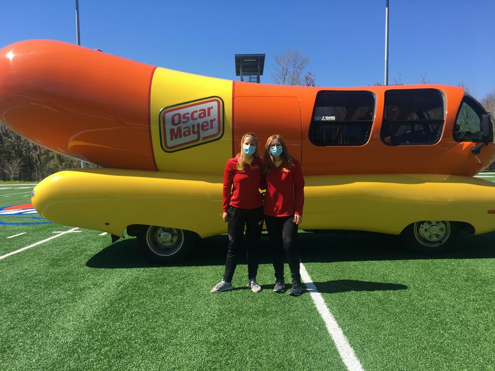 <p>Molly Swindall, left, and Maggie Thomas, right, two of the 12 hotdoggers of Class 33, arrived at UF in the Wienermobile to recruit the next class of hotdoggers.</p>