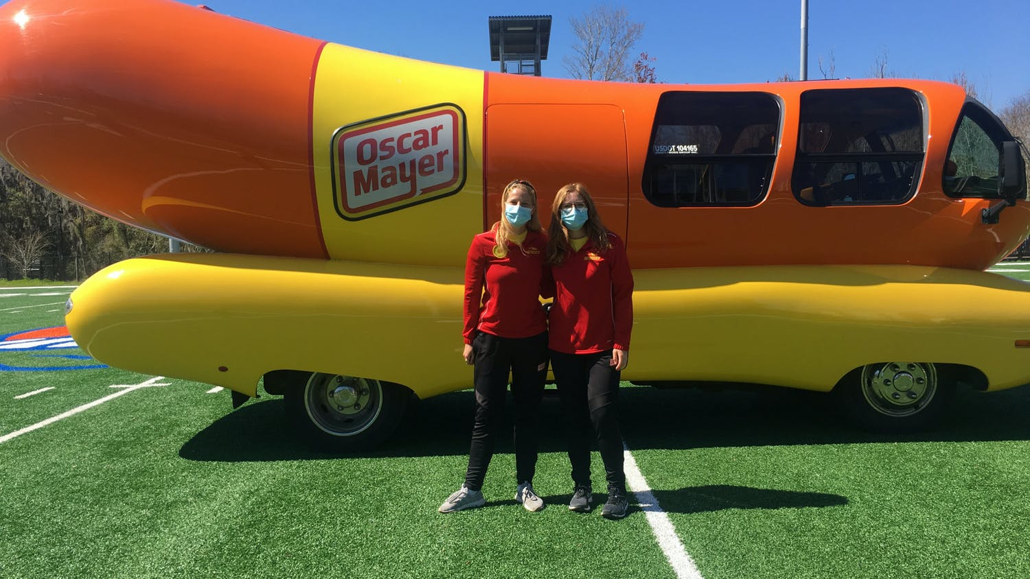 Molly Swindall, left, and Maggie Thomas, right, two of the 12 hotdoggers of Class 33, arrived at UF in the Wienermobile to recruit the next class of hotdoggers.