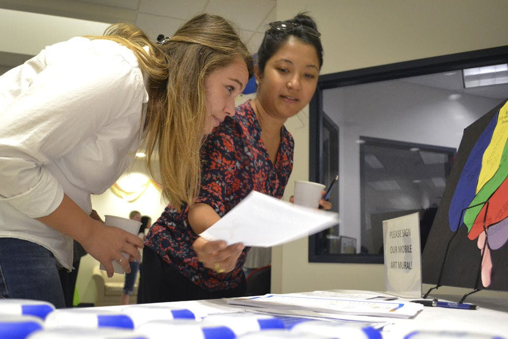 <p>Mirsada Serdarevic (left), 24, and Shivani R. Khan, 28, both UF epidemiology PhD students, peruse an information table at UF HealthStreet during the Our Community, Our Health event Sept. 24, 2015. Khan picked up a flier for a 6-week dance program held by the UF Center for Arts in Medicine, which both girls said they will attend.</p>