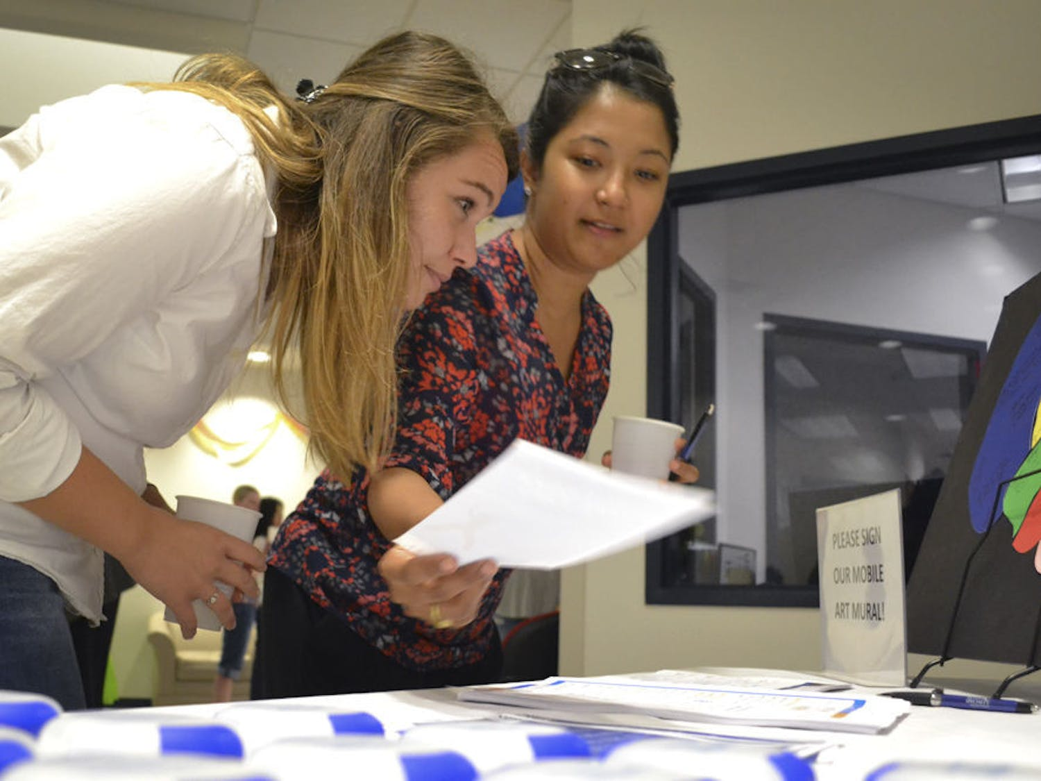 Mirsada Serdarevic (left), 24, and Shivani R. Khan, 28, both UF epidemiology PhD students, peruse an information table at UF HealthStreet during the Our Community, Our Health event Sept. 24, 2015. Khan picked up a flier for a 6-week dance program held by the UF Center for Arts in Medicine, which both girls said they will attend.
