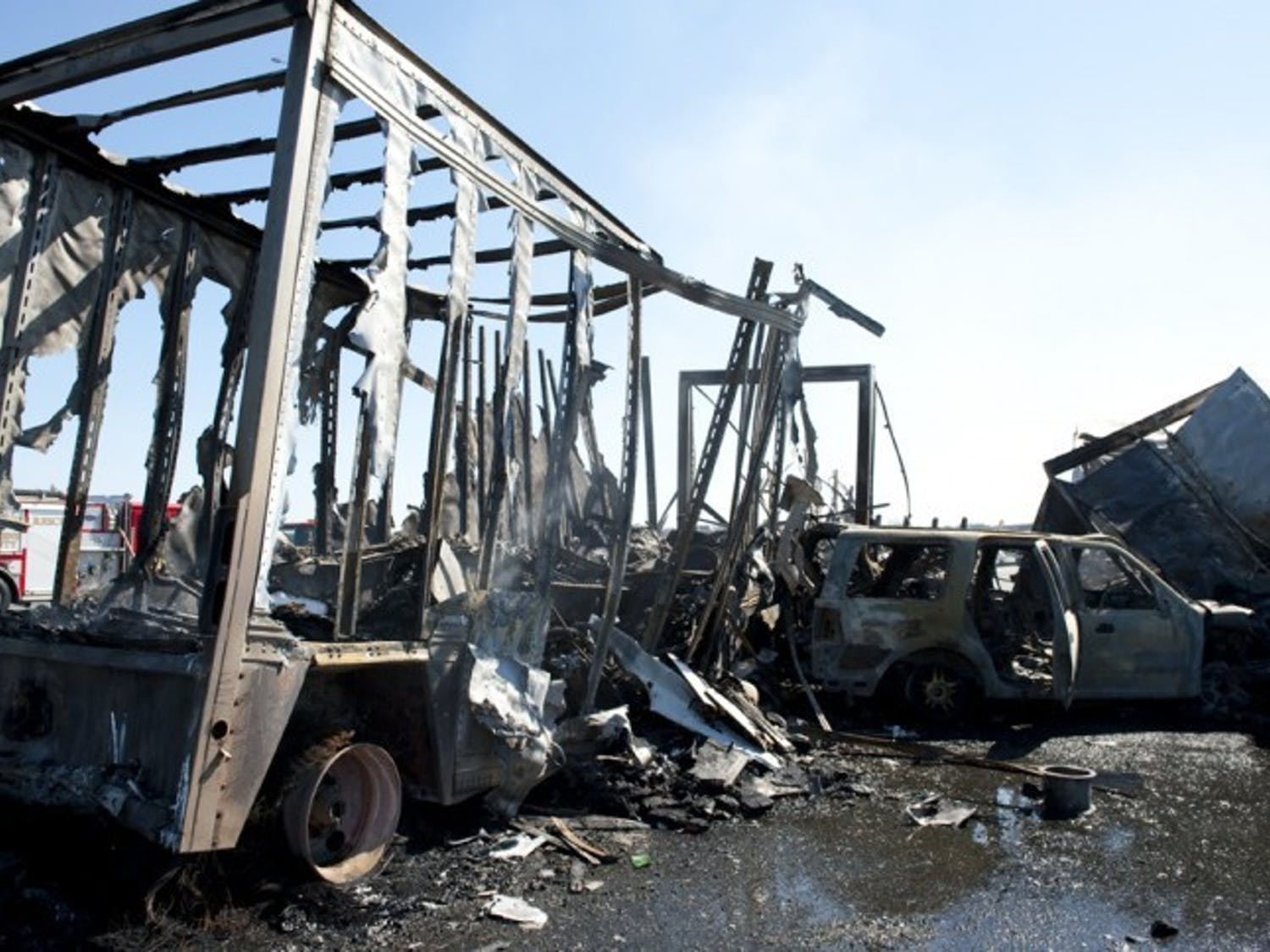 The charred wreckage of a semitrailer and an SUV sit on Interstate 75 Sunday afternoon. The wreck claimed at least ten lives.