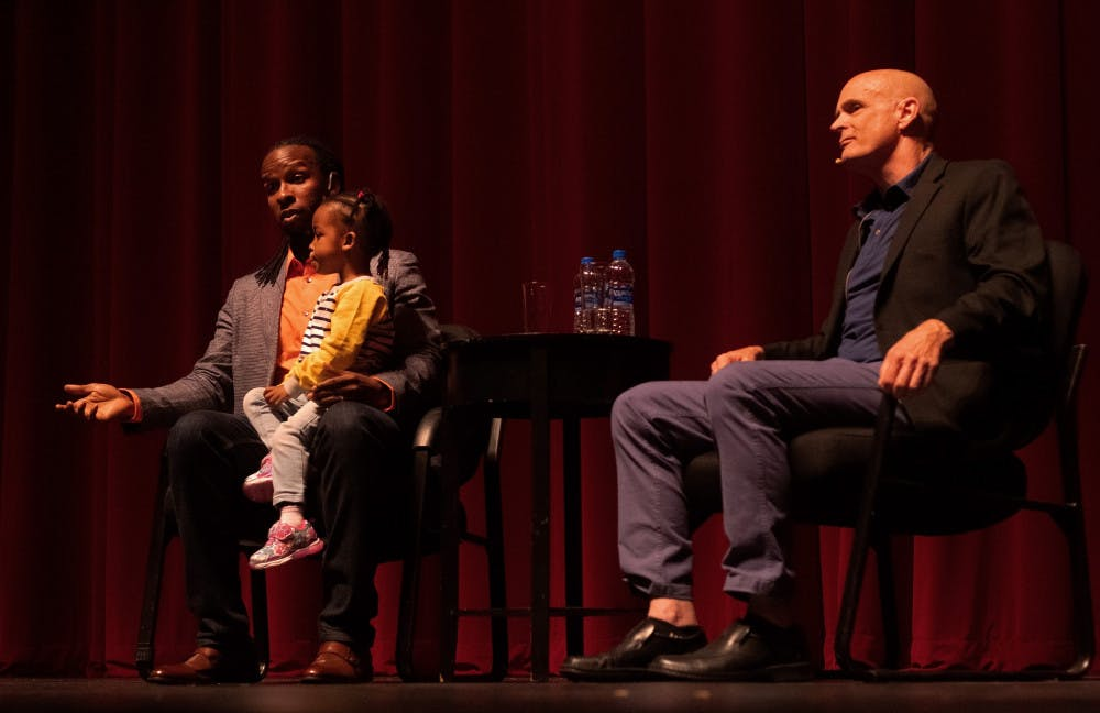 "<p dir=""ltr"">Ibram X. Kendi answers an audience question during a question and answer session moderated by author and history professor Jack Davis while Kendi's daughter sits in his lap at the Phillips Center for the Performing Arts Thursday night. About 1,230 people attended the event.</p>"