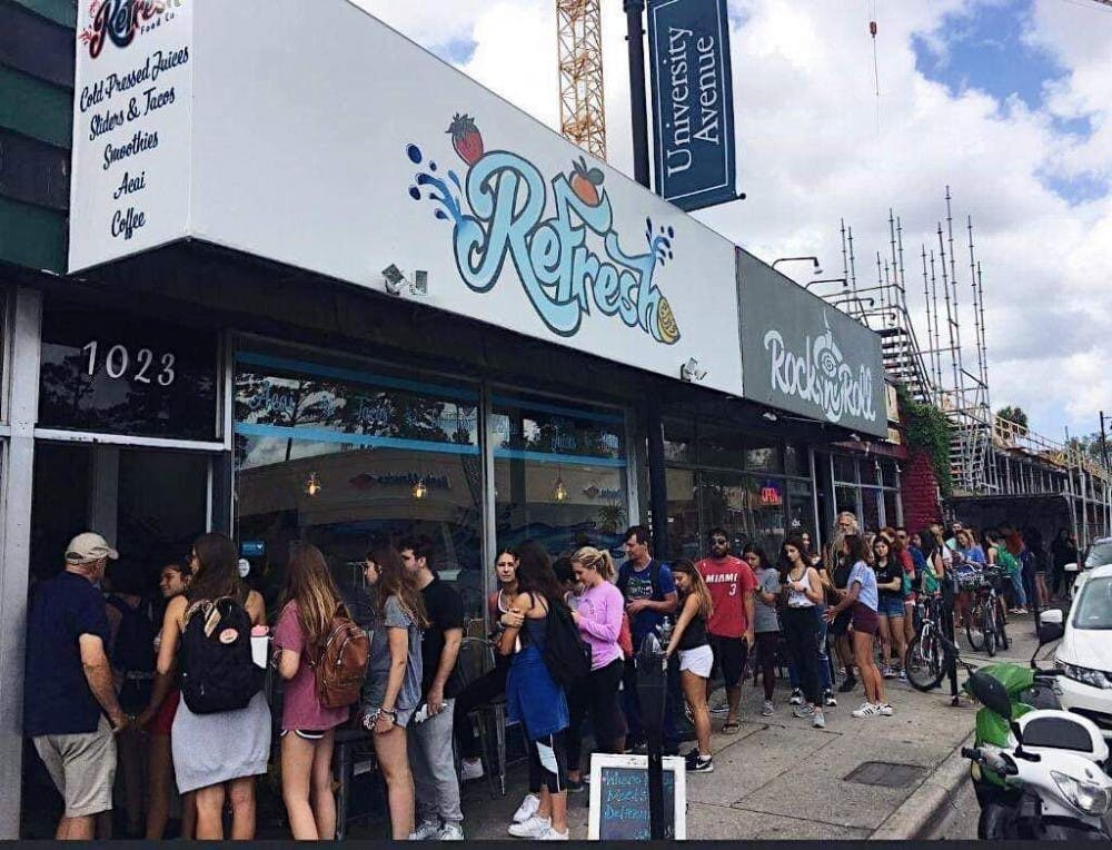 <p>A line of customers wait to enter ReFresh Food Co. during their grand opening.</p>