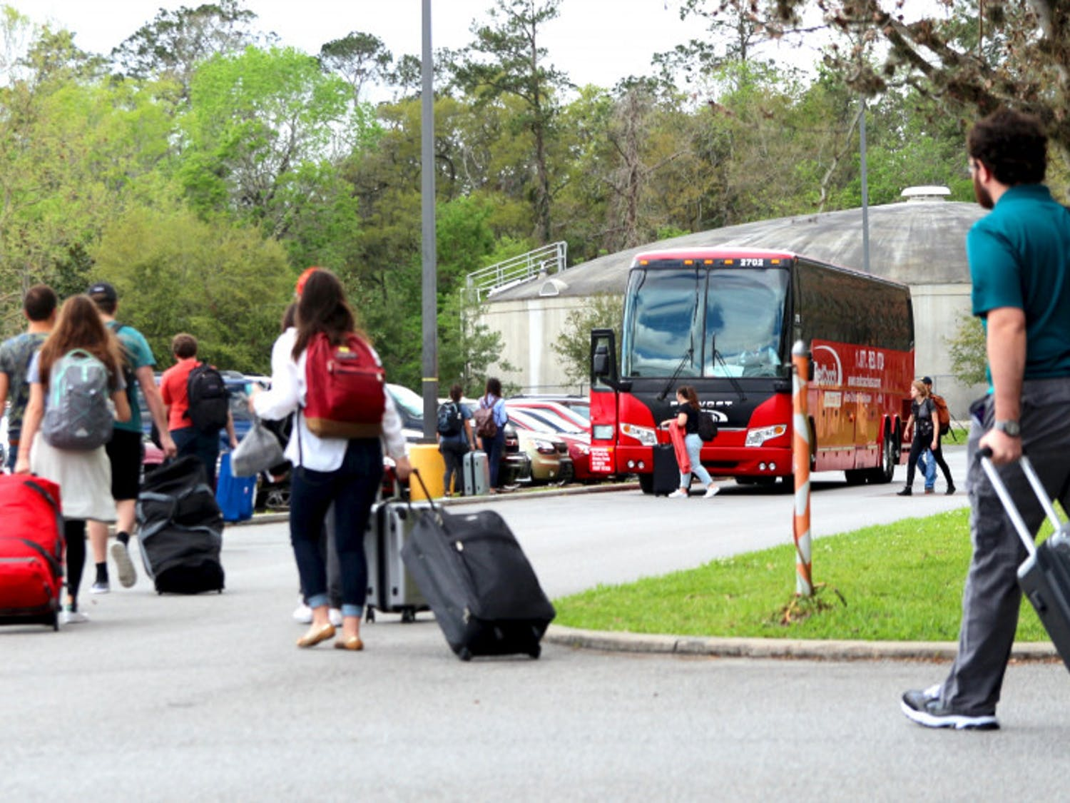 Students and other passengers walk toward a RedCoach bus to begin boarding Thursday afternoon at the Commuter Lot as UF will begin its Spring Break this upcoming week.