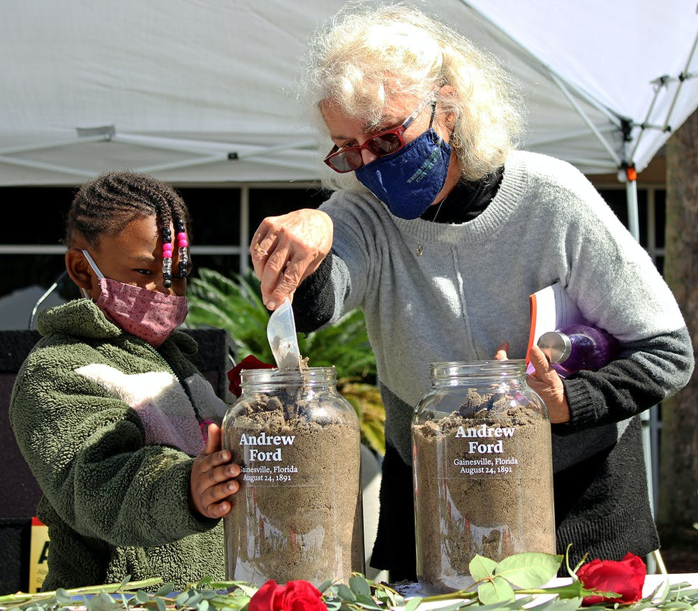<p>Alachua County Commissioner Marihelen Wheeler, 69, (right) and her granddaughter Tashayla Downer, 8, (left) fill a jar with soil to honor Andrew Ford at the Gainesville Soil Collection Ceremony on Feb. 20, 2021. Ford was lynched in Gainesville on Aug. 24, 1891, according to a pamphlet from the Alachua County Community Remembrance Project.</p>