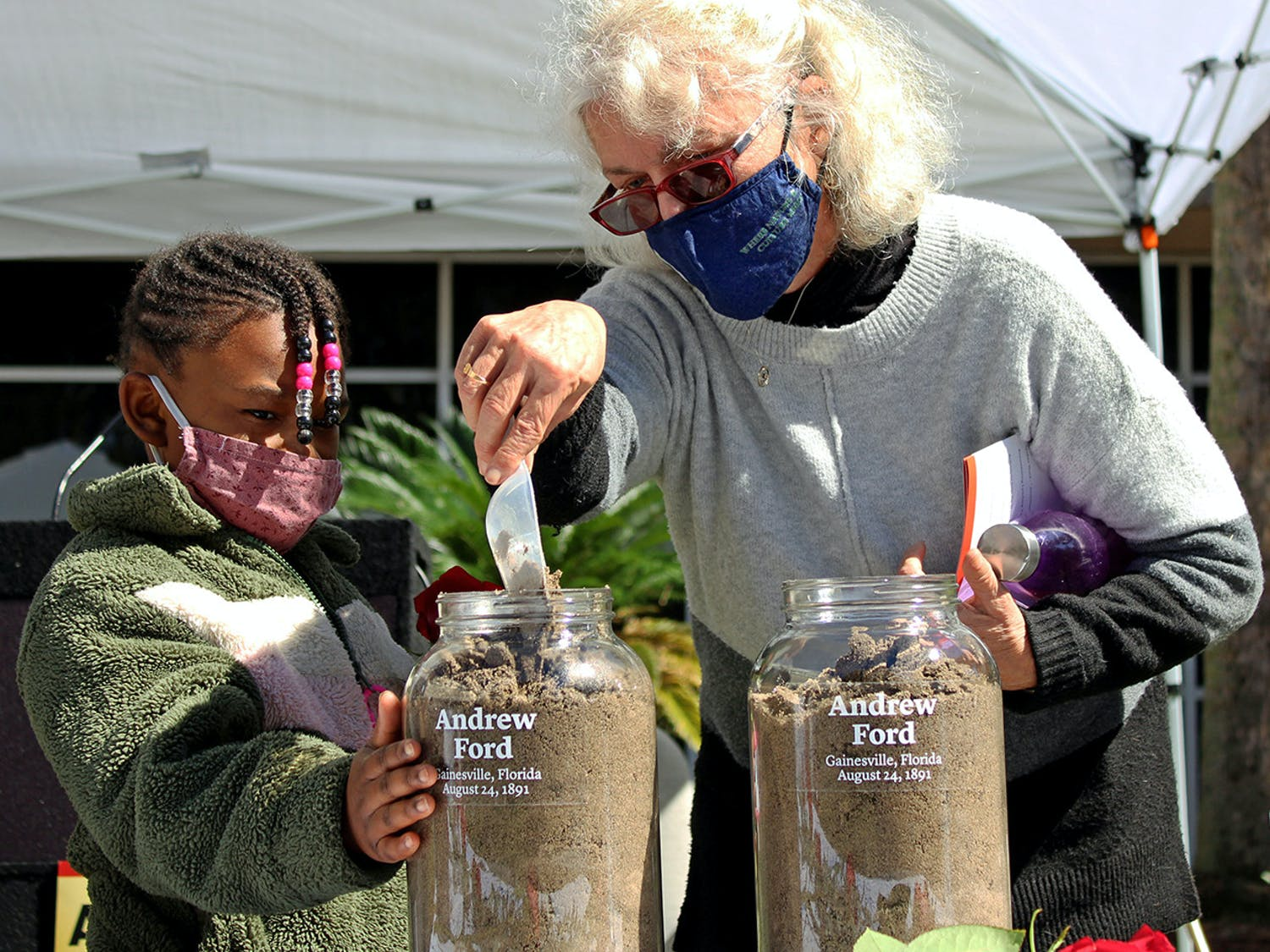Alachua County Commissioner Marihelen Wheeler, 69, (right) and her granddaughter Tashayla Downer, 8, (left) fill a jar with soil to honor Andrew Ford at the Gainesville Soil Collection Ceremony on Feb. 20, 2021. Ford was lynched in Gainesville on Aug. 24, 1891, according to a pamphlet from the Alachua County Community Remembrance Project.