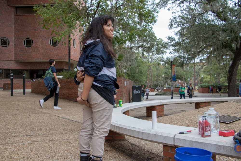 """<p>Sophia Ahmed, a UF materials science and engineering sophomore, stands near the rock sculpture on Turlington Plaza applying washable red dye on her pants. Ahmed, 20, is an organizer for """"Are You Seeing Red?,"""" and said the point is to raise awareness about the lack of free menstrual products on campus.</p>"""