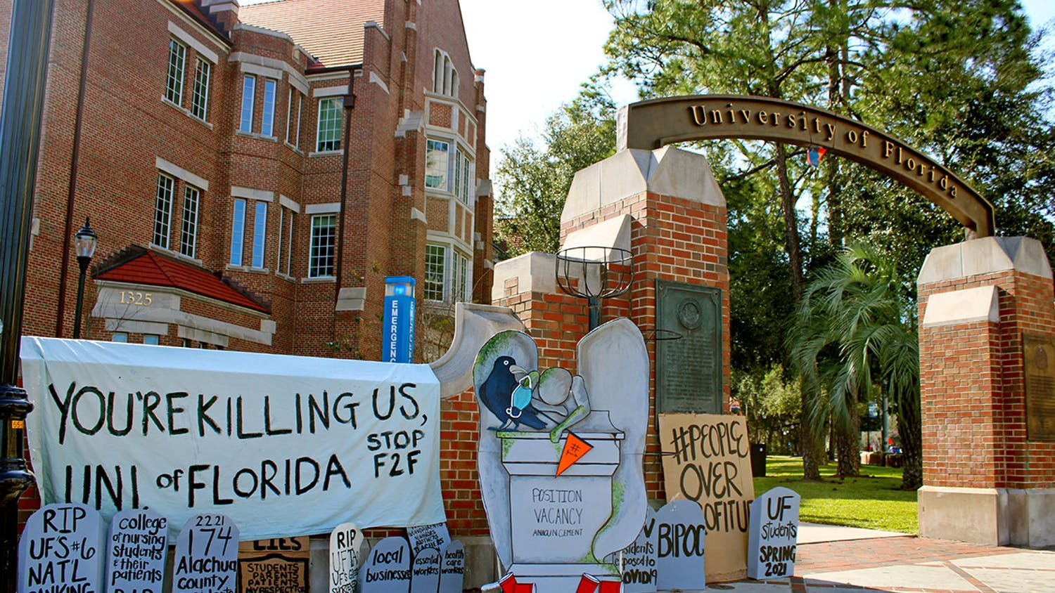 A collection of tombstone shaped signs and a banner calling for the end of in-person classes at the University of Florida was set-up on the corner of 13th Street and University Avenue on Thursday, Feb. 4, 2021.