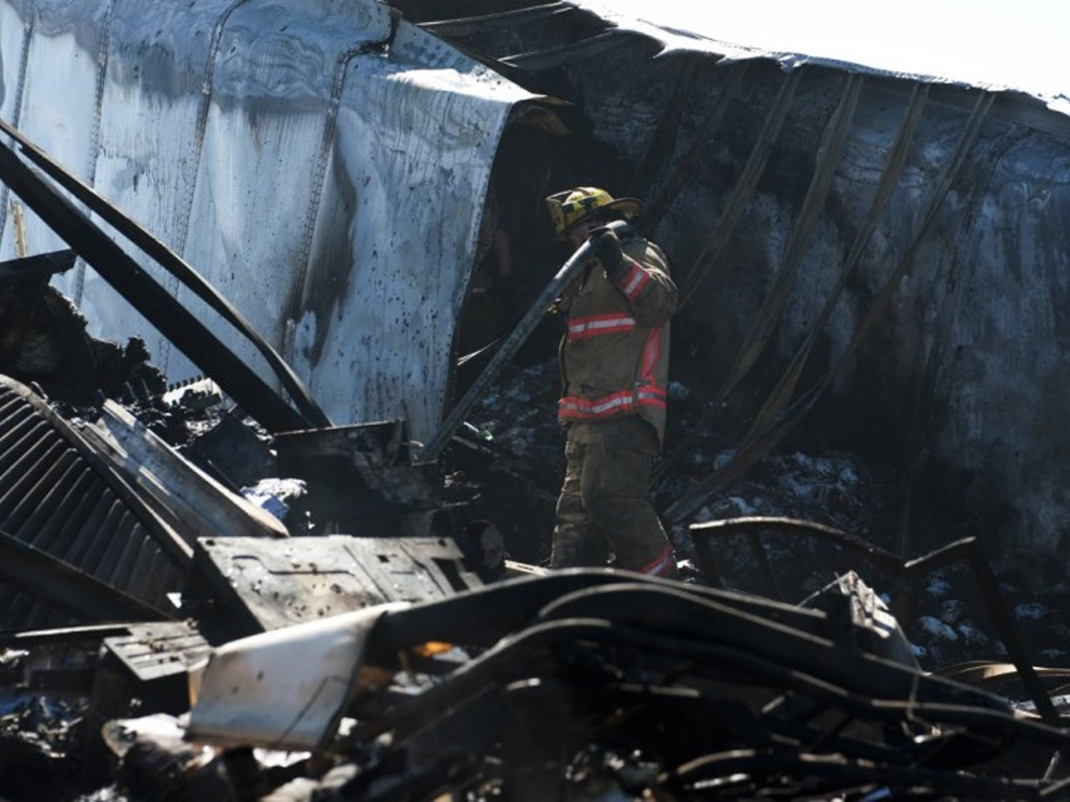 An Alachua County Fire Rescue Worker carries a hose through the wreckage of a semitrailer involved the southbound accident on Interstate 75 Sunday afternoon. The north and southbound accident claimed a total of 10 lives.