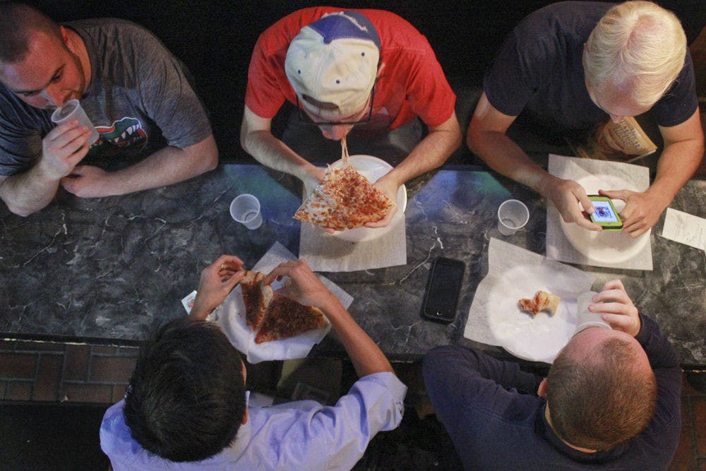 """<p>Alex Landry (top center), a 23-year-old UF alum, chews cheesy pizza with his group of friends who call themselves """"The Gumby Guys"""" at Gumby's Pizza's 30th anniversary on Oct. 26, 2015. The group has been meeting at Gumby's every Wednesday after Bible study for about 7 years. On Wednesday's, Gumby's has $0.50 pizza rolls. """"For college kids,"""" Landry said, """"it's the dream.""""</p>"""