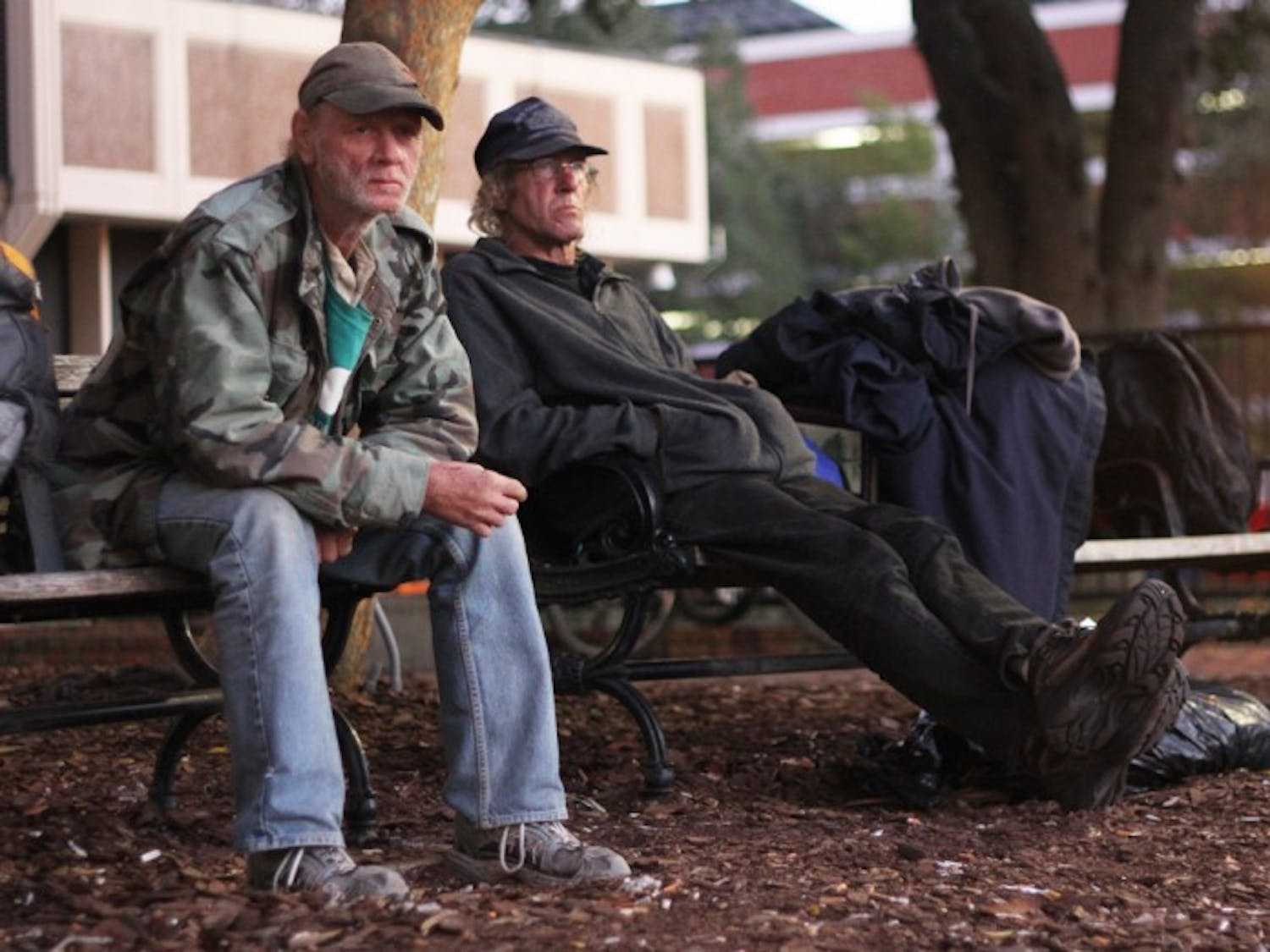 John Roberts, 56, left, and Daniel Walters, 53, sit on a bench on Bo Diddley Community Plaza on Friday night. Temperatures will dip into the low 40s over the next few nights.