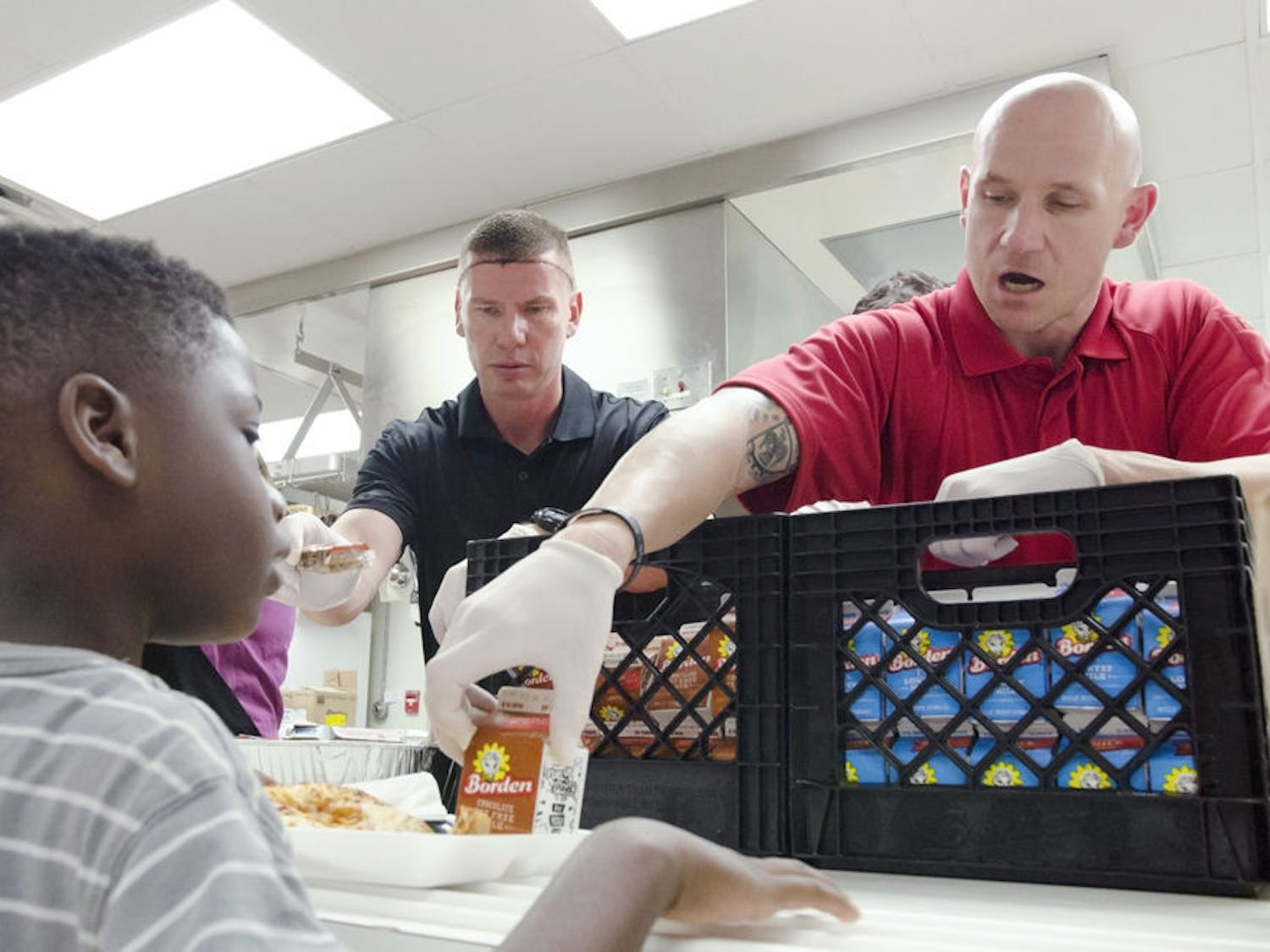 [FILE PHOTO] John Nordman, right, hands 8-year-old Micah Reed a chocolate milk at the Reichert House on Tuesday. Nine newly hired police officers served 128 students lunch.