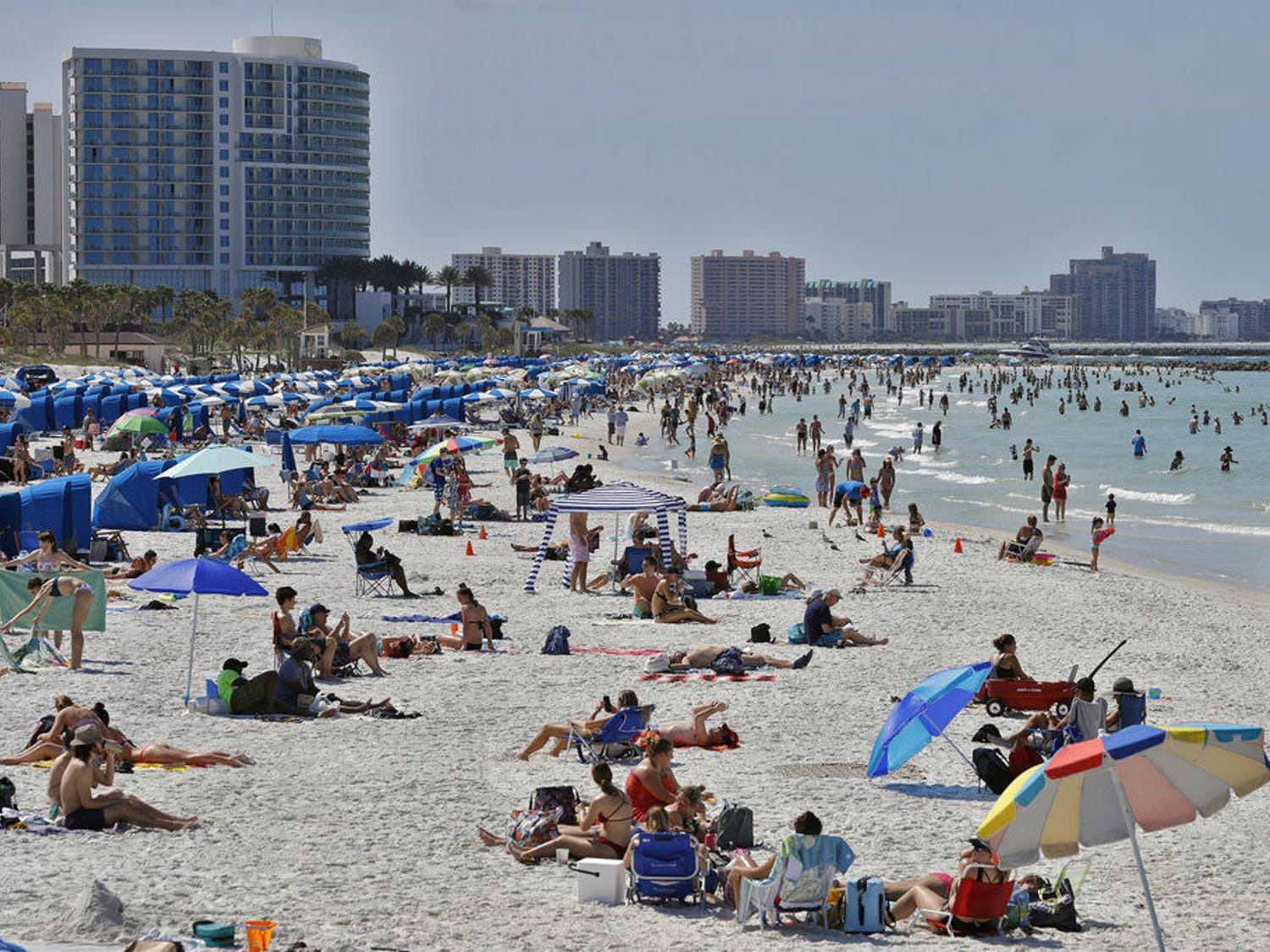 Visitors enjoy Clearwater Beach, Wednesday, March 18, 2020, in Clearwater Beach, Fla. Beachgoers are trying to keep a safe distance from each other by keeping a space of 6 to 10 feet (2 to 3 meters) between family groups to help protect from the spread of the coronavirus. (AP Photo/Chris O'Meara)