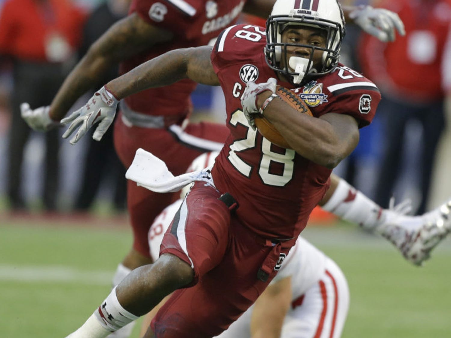 In this Jan. 1, 2014, file photo, South Carolina running back Mike Davis (28) gains yardage against Wisconsin during the second half of the Capital One Bowl NCAA college football game in Orlando, Fla. Steve Spurrier says 1,000-yard rusher Mike Davis hadn't practiced last week and might not be ready when the ninth-ranked Gamecocks open the season against No. 21 Texas A&M tonight.