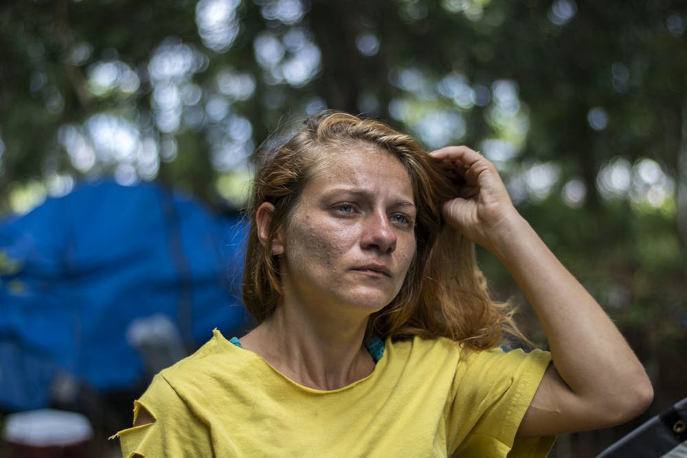 """<p><span id=""""docs-internal-guid-fdf38560-7fff-44b5-e7dd-7f173f063011""""><span>Amanda Smith, a 31-year-old Dignity Village resident, stands in front of her camp located on the outskirts of the 10-acre property. Smith has lived there for four months. She wants to stay in Gainesville once it closes on Jan. 1, though she does not know where she will go.</span></span></p>"""