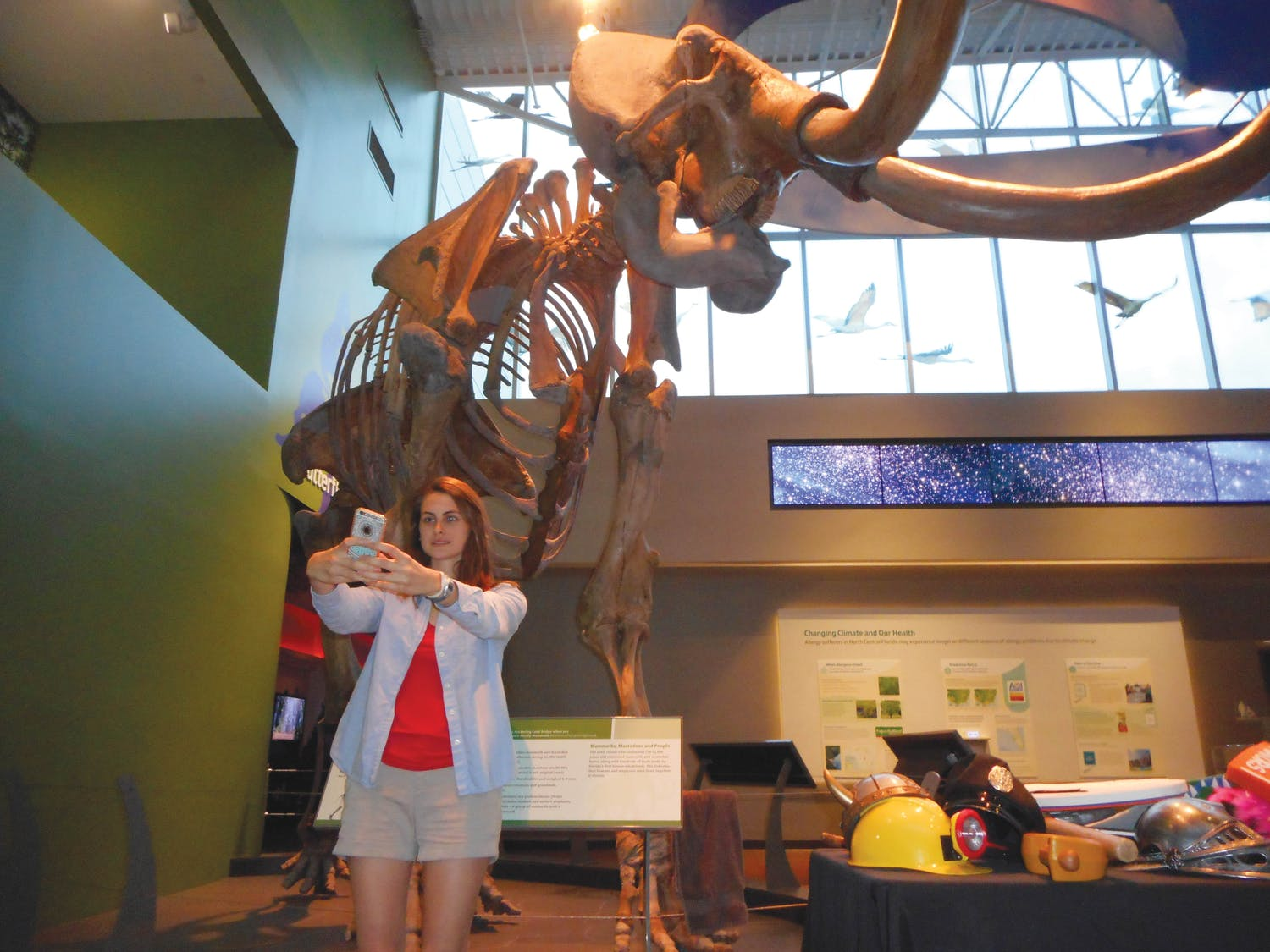 """Jaime Benedict, a 20-year-old UF nursing junior, snaps a selfie in front of the mammoth skeleton at the Florida Museum of Natural History during """"Museum Selfie Day."""""""