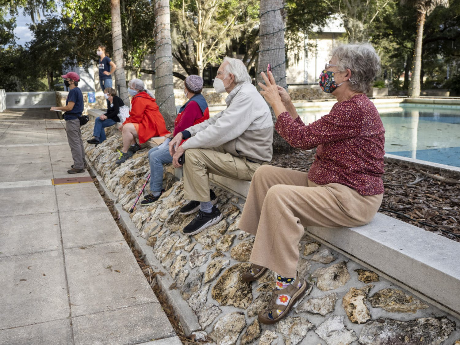 A group of people are seen listening to speakers from the Blue Wave Coalition in Alachua County, who organized a Protect the Results rally held at the Alachua City Hall on Wednesday, Nov. 4, 2020. (Emily Felts/Alligator Staff)